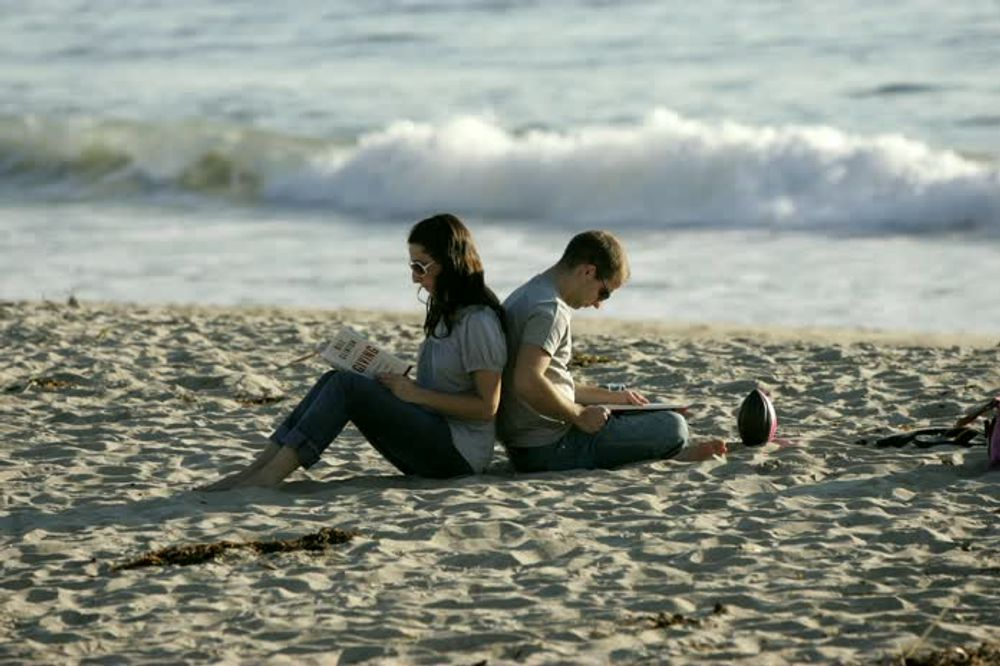 title: Cute Couple Reading on the Sandy Laguna Beach of Southern Orange County