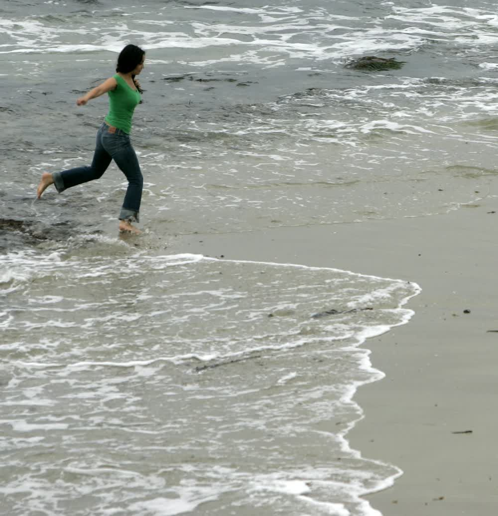 title: Lady Running Barefoot of the Sandy Beach Shores of La Jolla in San Diego