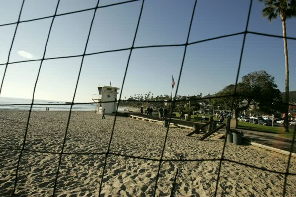 title: Peering through the Holes of a Net in the Laguna Beach Sandy Playground in California