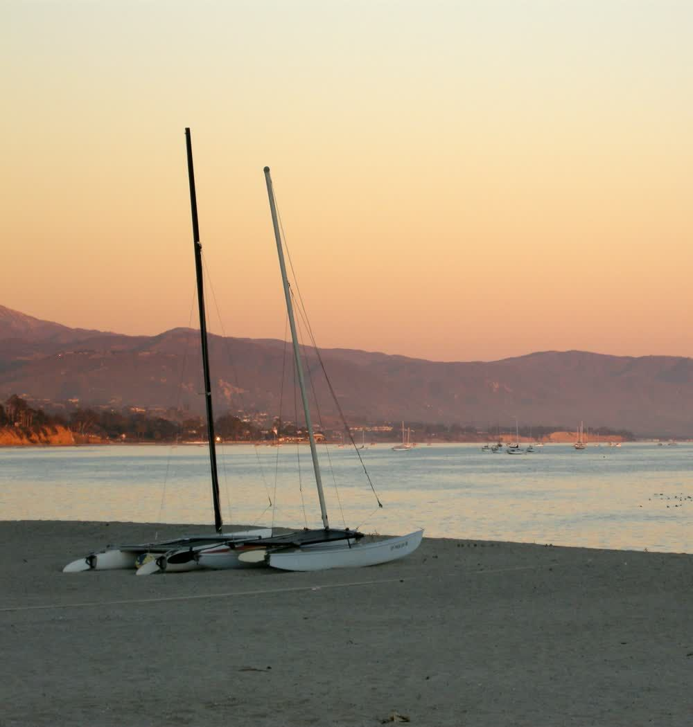 title: Sailing Boats Parked on the Sand at Newport Beach at Dusk