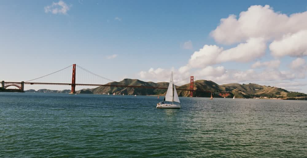title: Small White Boat Sailing by the Golden Gate Bridge