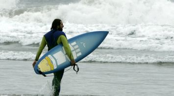 title: Surfer Holding Board on the Sandy Shores of Beach La Jolla in San Diego
