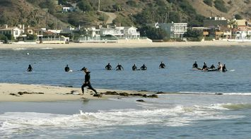 title: Surfers in Black Suits at Malibu Beach