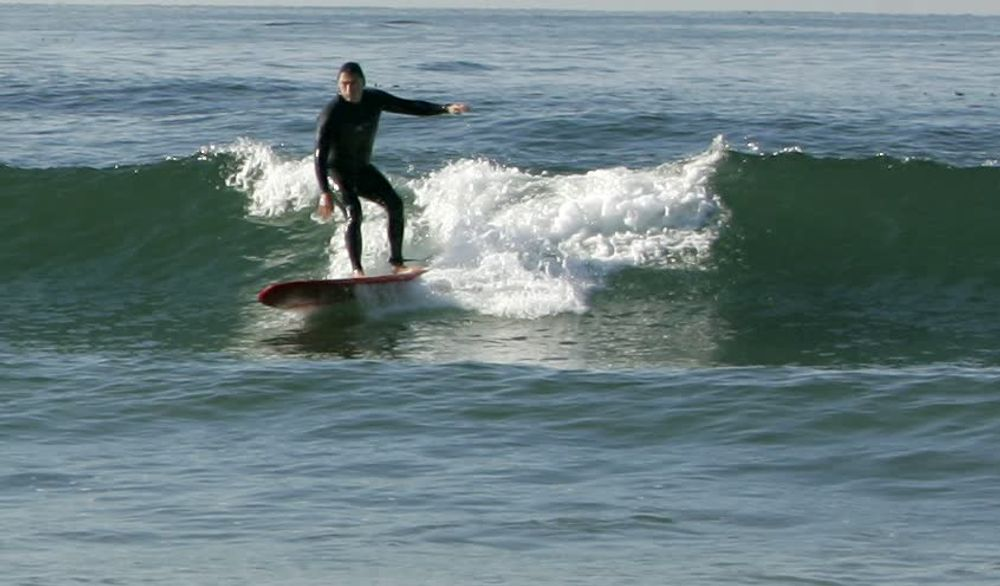 title: Talented Surfer on a Small Wave at the Beach