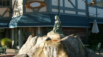 title: Bronze Lady Statue Sitting Atop a rock Fountain