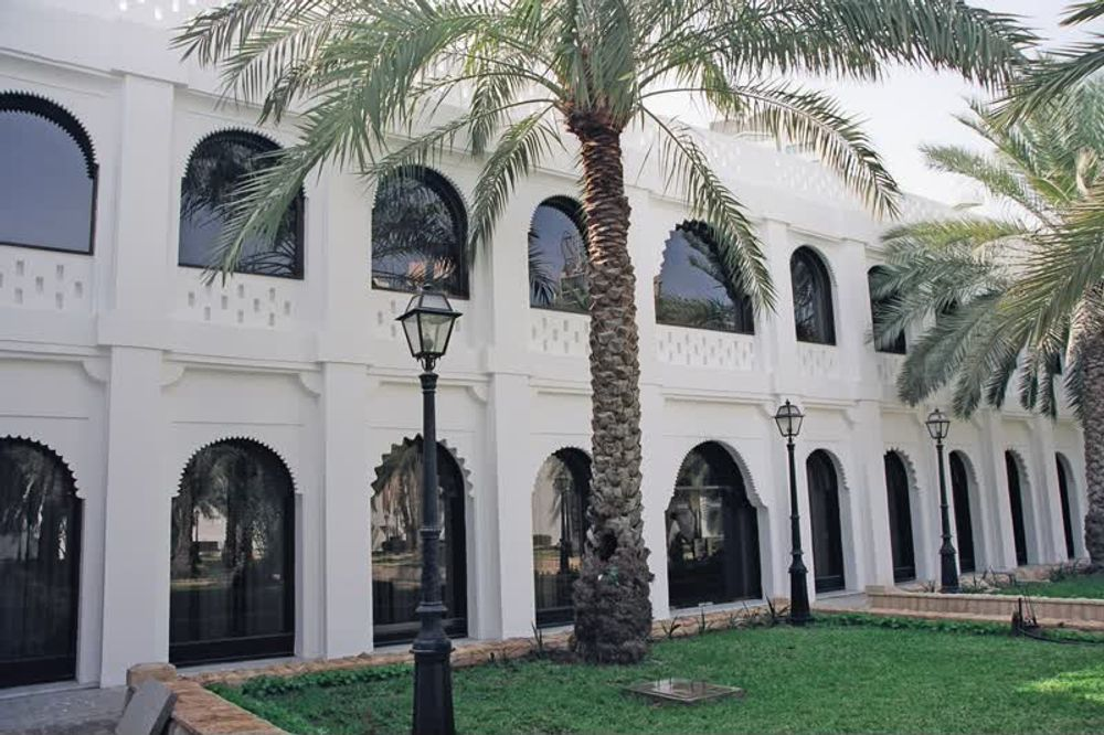 title: Beautiful Architecture and Palm Trees in the Lovely Garden of Qasr al Hosn