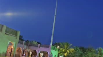 title: Colorful Green and Purple Lights by the UAE Flag