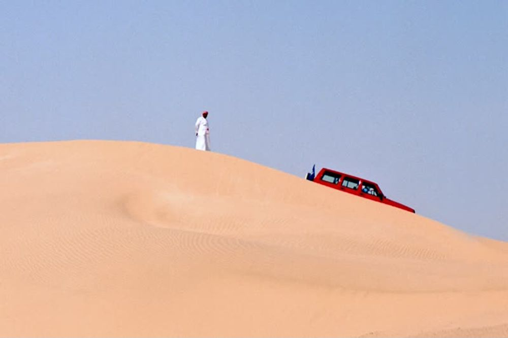 title: Local wearing Traditional Arabic Male Costume on the Sand Dune