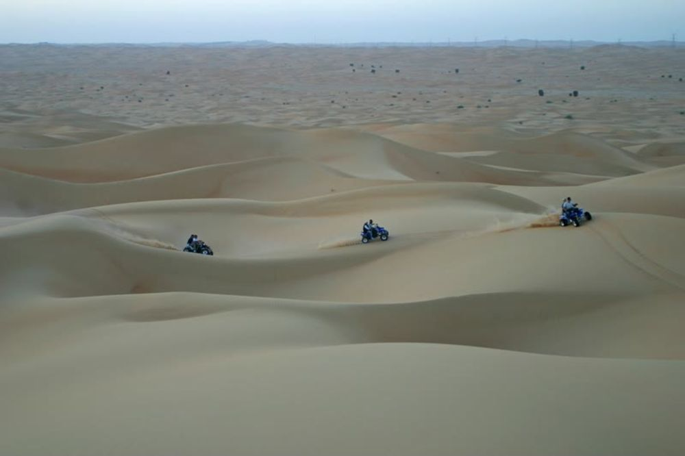 Three ATV Cars Riding on the Desert Dunes