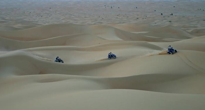 title: Three ATV Cars Riding on the Desert Dunes