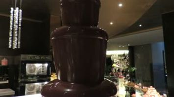 title: Chocolate Fountains Dessert Table with Fruits and Marshmallows on Skewer Sticks