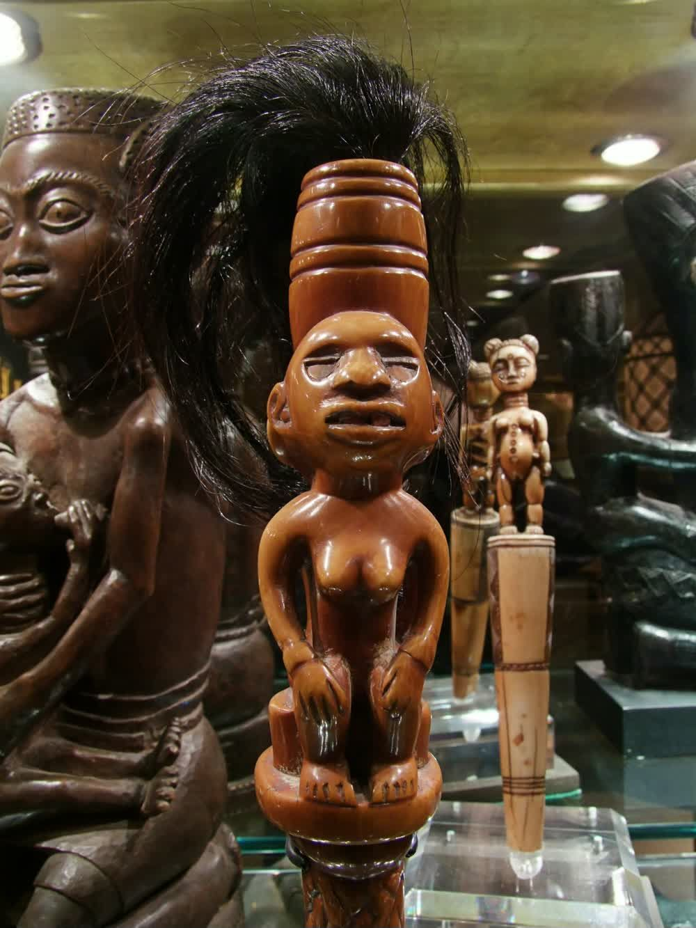 title: Wooden Statue with Real Black Hair in Poly Tail