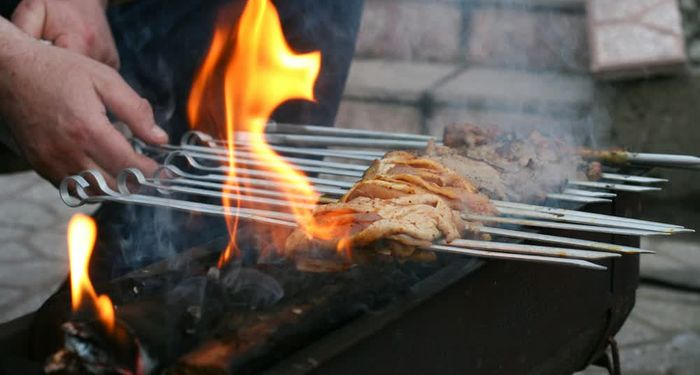 title: Traditional Shashlyk Skewers on the Smoky Grill in Russian Restaurant