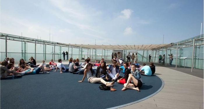 title: Crowded Terrace on Tour Montparnasse 56 on a Sunny Day