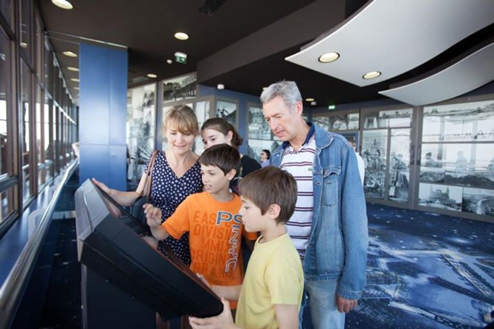 title: Family Enjoying the Interactive Display Units at Tour Montparnasse 56