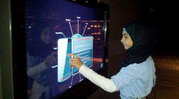 title: Female Student Interacting with Multitouch Table at MIM Museum