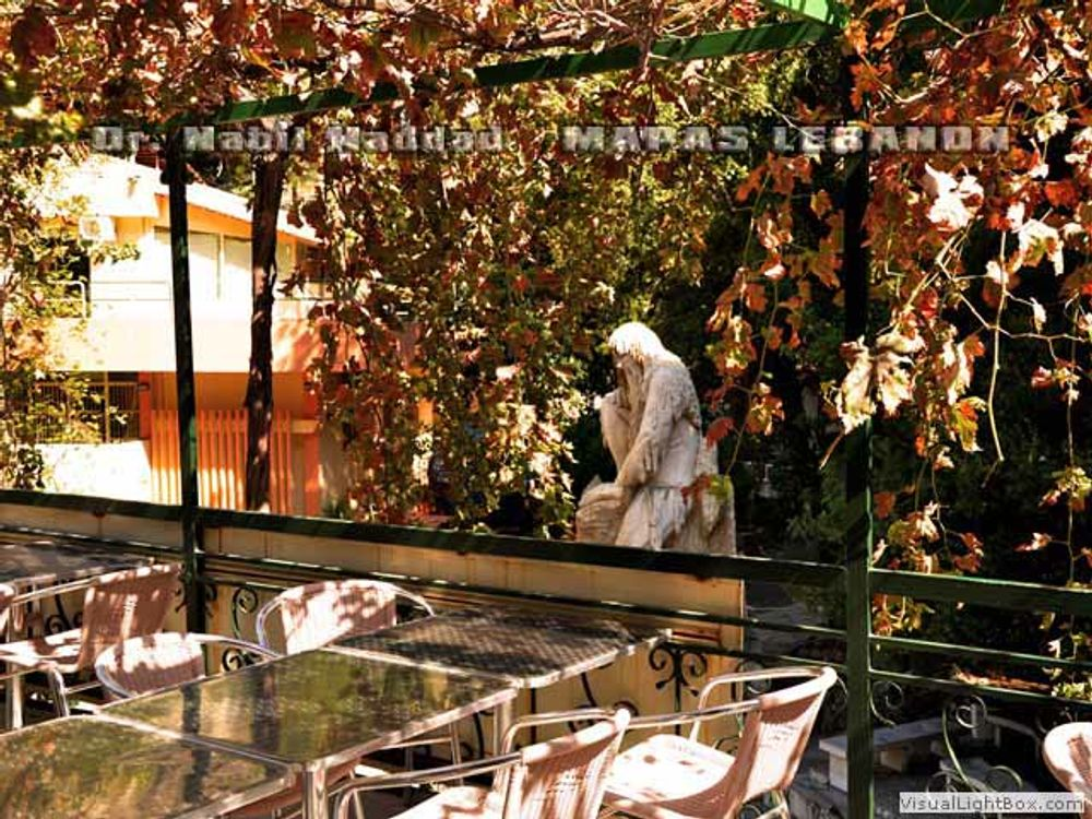 title: Outdoor Seating of Restaurant by Statue