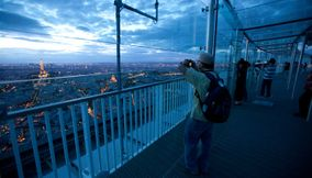 title: Visitor Taking a Picture of Paris in the Evening from the 56th Floor of the Tower of Montparnasse