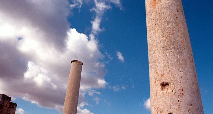 title: White Clouds Passing Over Inscribed Stone Columns of the Abandoned City Palace