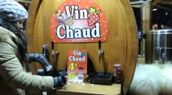 title: Video of Vendor at the Vin Chaud Kiosk Pouring us a Glass of Hot Wine in the Winter
